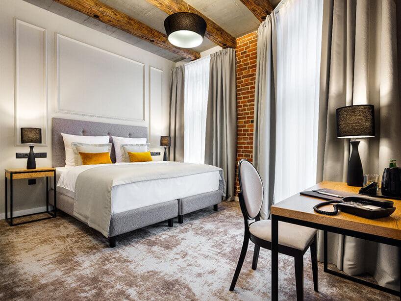 Wawel Queen pokój hotelowy zszarą wykładziną, łóżkiem oraz krzesłem stolikiem