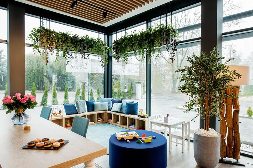 ibis Styles Santorini hotelowa restauracja stoliki przy oknie zkwiatami na wiszącej doniczce