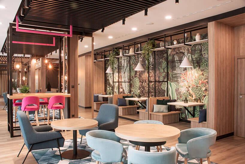 ibis Styles Santorini hotelowa restauracja zfotelami istolikami iróżowym krzesłem wtle