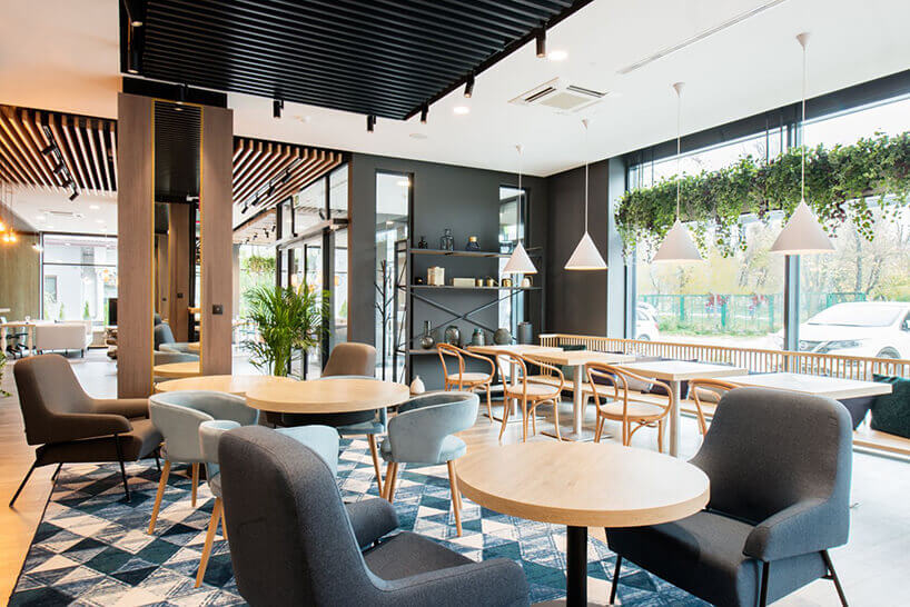 ibis Styles Santorini hotelowa restauracja zszarymi fotelami istolikami