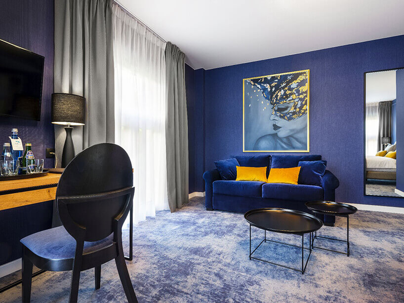 Wawel Queen pokój hotelowy zniebieską kanapą iścianą, obrazem iżółtymi poduszkami