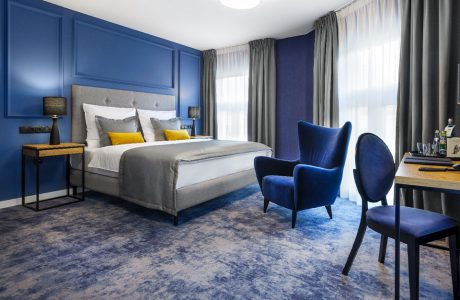 ibis Styles Santorini niebieski fotel w pokoju hotelowych z dużym łóżkiem z żółtymi poduszkami