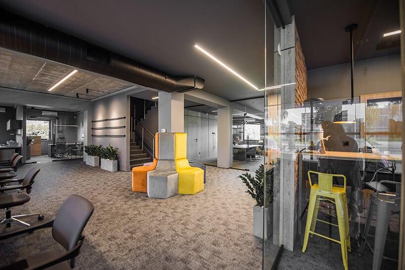 kolorowe siedziska przymocowane do betonowego słupa windustrialnym biurze