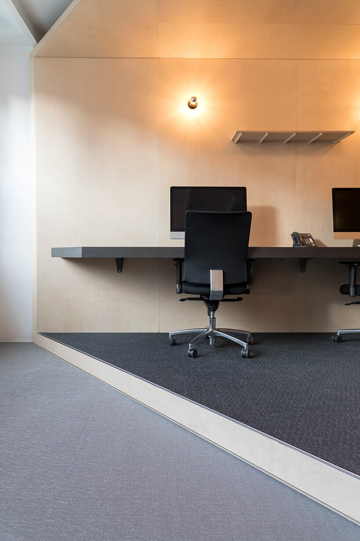 szara wykładzina na jasnej podłodzee wpomieszczeniu zkomputerami ikrzesłami