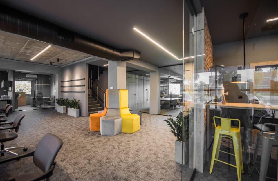 kolorowe siedziska przymocowane do betonowego słupa w industrialnym biurze