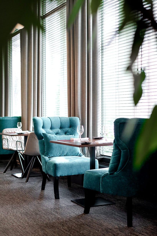 ciemne wykładziny winylowe od 2tec2 we wnętrzu restauracji zbrązowymi stolikami iniebieskimi eleganckimi fotelami
