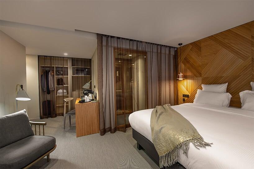 jasne wykładziny winylowe od 2tec2 wnowoczesnym wnętrzu pokoju hotelowego zdużym łóżkiem imałym drewnianym biurkiem