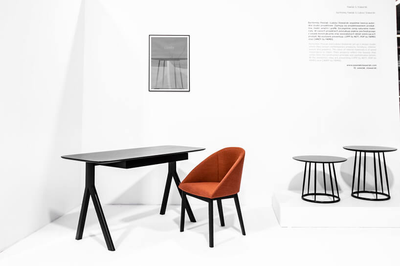 czarne małe biurko obok pomarańczowego fotela na czarnych nogach
