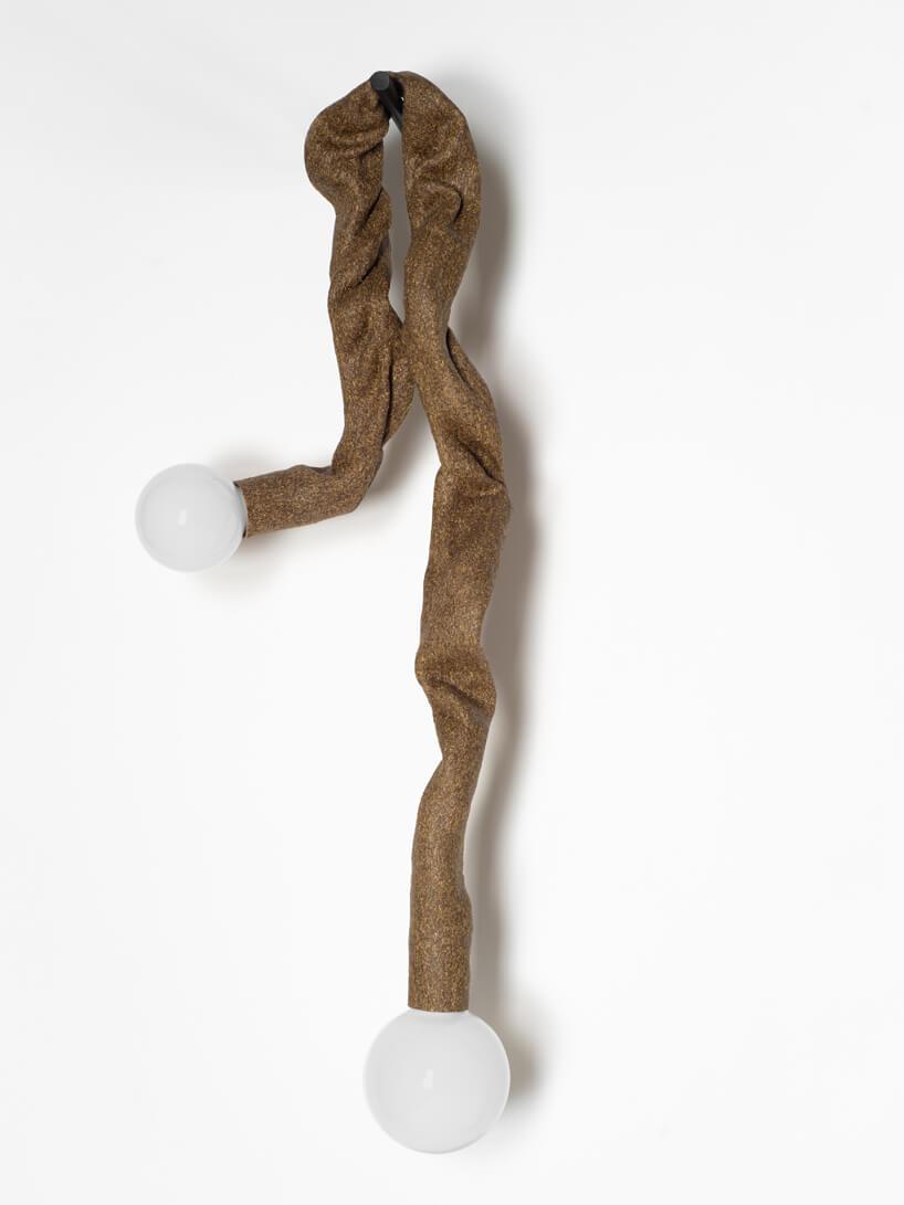 wyjątkowa brązowa lampa Senila od High Society zawieszona na haku na białej ścianie