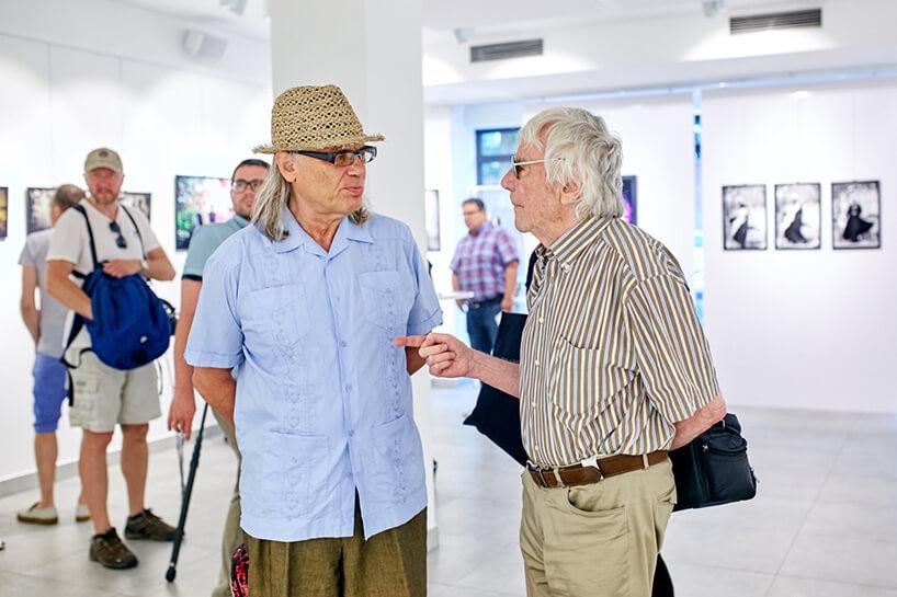 """dwóch mężczyzn wtrakcie rozmowy podczas wernisażu wystawy zdjęć """"Kora"""""""