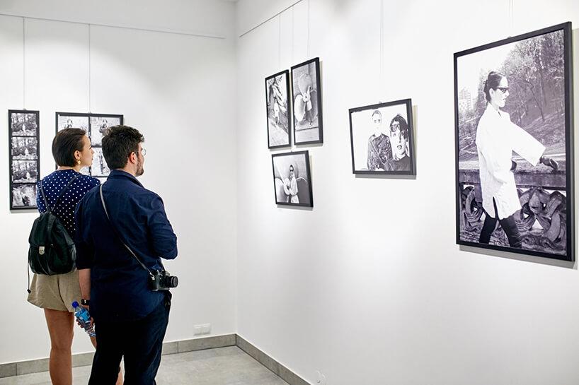 """dwoje ludzi podczas oglądania zdjęć na wystawie """"Kora"""""""