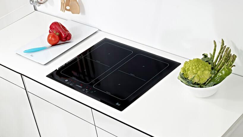 czarna płyta indukcyjna wbiałym blacie kuchennym