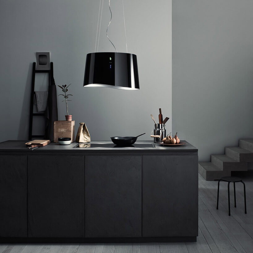 ciemna kuchnia zwyspą iczarnym okapem wkształcie lampy wiszącej