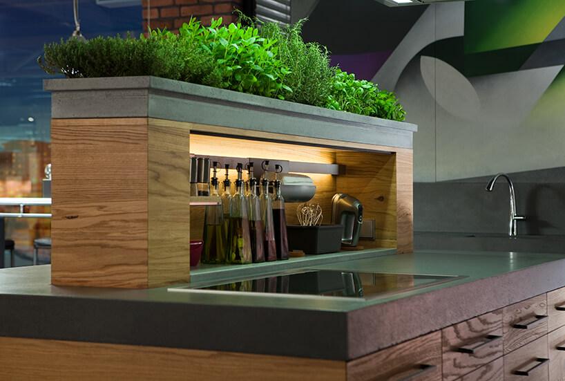 kuchnia premium od ernestrust wyjątkowa drewniana szafka na kamiennej wyspie zkamienną donnicą na zioła ugóry