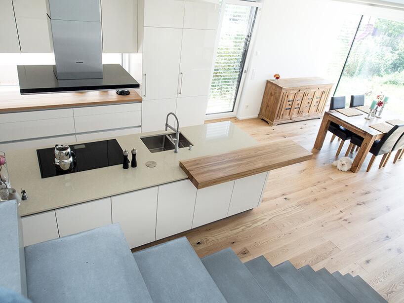 kuchnia premium od ernestrust zbłyszczącymi idrewnianymi elementami widziana zbetonowych schodów