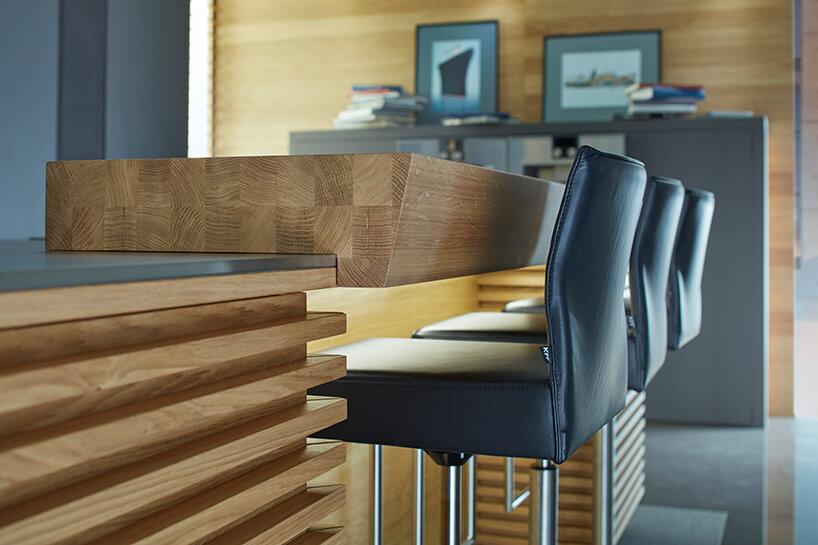 kuchnia premium od ernestrust eleganckie drewniane wykończenia wyspy kuchennej itrzy wysokie czarne krzesła