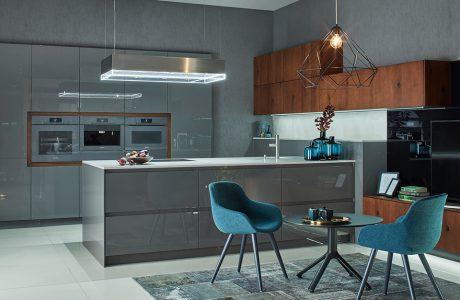 kuchnia premium od ernestrust szare błyszczące meble z dużą wyspą i dwoma niebieskimi fotelami i małym okrągłym stoliku