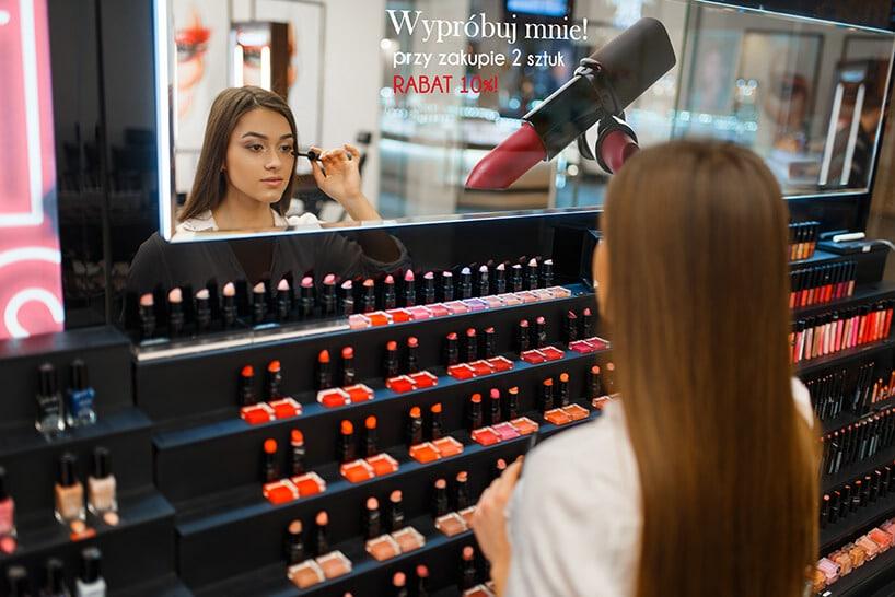 kobieta stojąca przy czarnych półkach zkosmetykami oraz przeglądająca się wlustrze