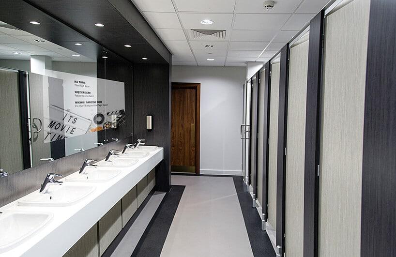 nowoczesna toaleta zlustrem zekranem oraz białym blatem zumywalkami ipasami na podłodze