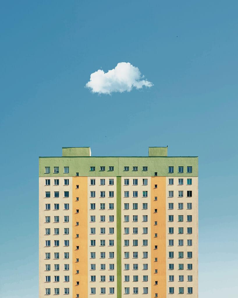 zdjęcie wysokiego bloku mieszkalnego wbeżowym kolorze zzieloną iżółtą linią pod małą chmurką