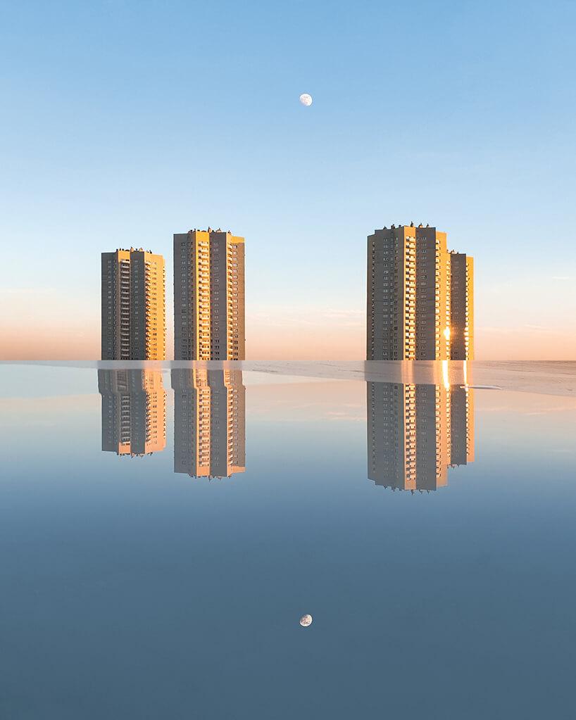 cztery żółte wieżowce na tle nieba zgórującym małym księżycem odbijające się na tafli kałuży
