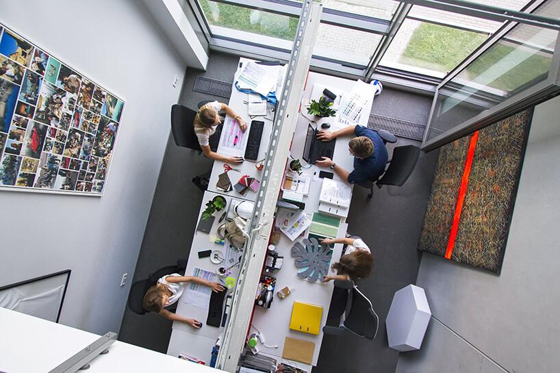 zdjęcie biura zgóry białe biurka wbiałym pomieszczeniu rząd białych podwójnych biurek przy dużych panoramicznych oknach