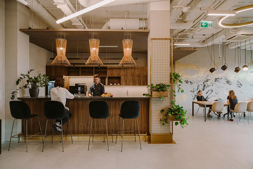 przestrzeń kuchenna zjadalnią wprzestrzeni open space zwysoką wyspą drewnianą