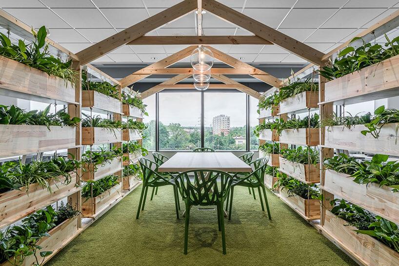 zielona aranżacja przestrzeni konferencyjnej otoczonej drewnianym donicami zzielonymi roślinami
