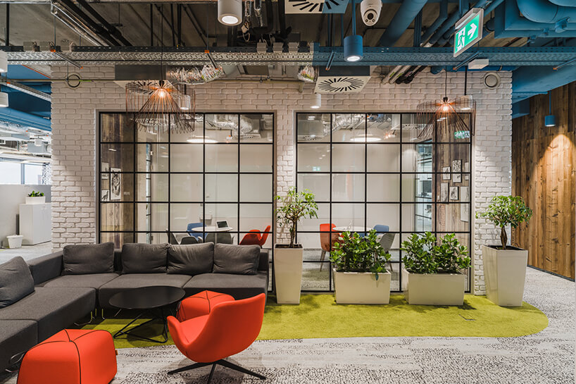 aranżacja przestrzeni open space do relaksu na tle oszklonej sali konferencyjnej