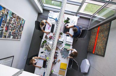 zdjęcie biura z góry białe biurka w białym pomieszczeniu rząd białych podwójnych biurek przy dużych panoramicznych oknach