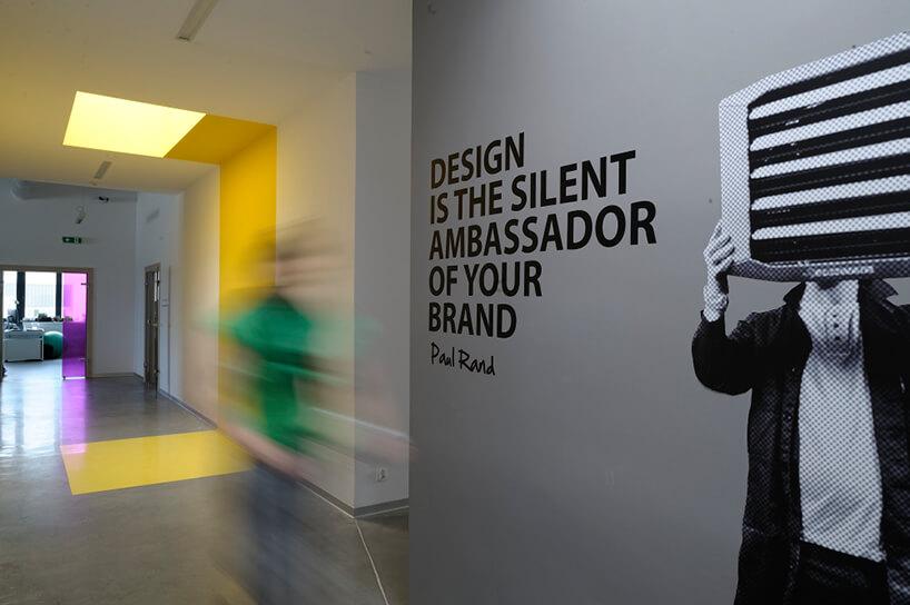 wnętrze biura znapisem na ścianie obok zdjęcia mężczyzny zakrywającego twarz klimatyzatorem