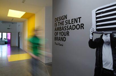wnętrze biura z napisem na ścianie obok zdjęcia mężczyzny zakrywającego twarz klimatyzatorem