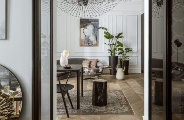 mieszkanie z zdobienia w starym stylu na lekko szarych ścianach przy meblach w czarnym piano black