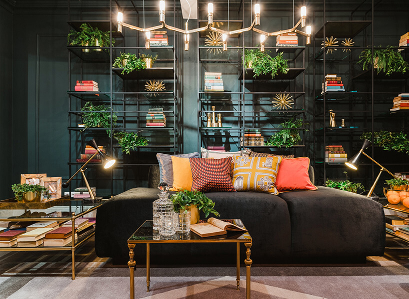 ciemna sofa zpoduszkami wzielonej aranżacji