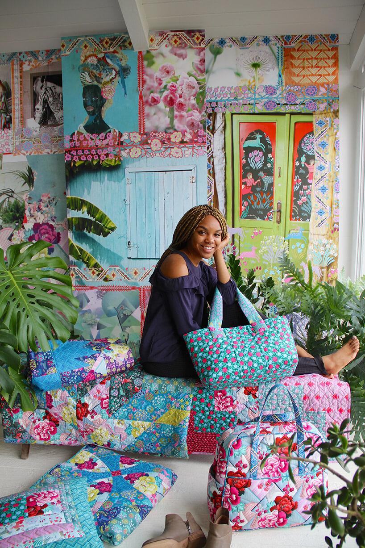 kobieta siedząca pośród wzorzystych tekstylii