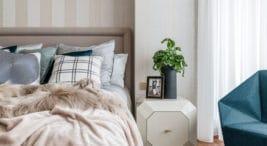 puszysty koc oraz szaro-białe poduszki przy szafce wformie kostki