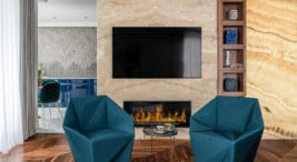 dwa morskie fotele wkształtach geometrycznych przy beżowej ścianie ztelewizorem