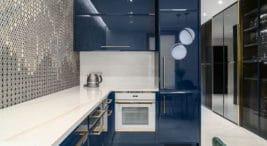 mała kuchnia zniebieskimi połyskowymi frontami ibiałym blatem