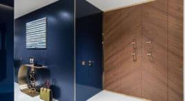 drewniana szafa obok niebieskiej połyskującej ściany