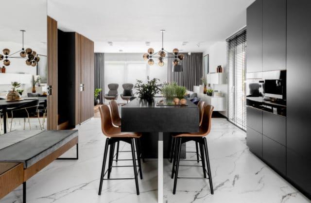wnętrze kuchni z wysokim stołem oraz krzesełkami drewnianymi oraz metalowymi nogami