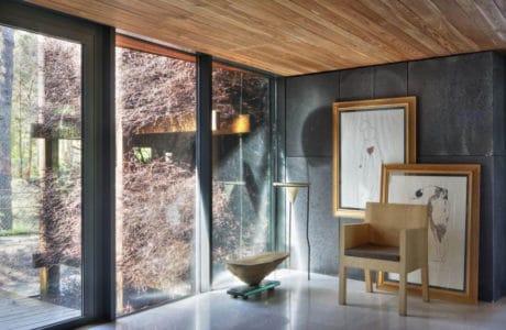 salon z drewnianym dachem z przeszkleniem oraz obrazami w drewnianych ramach