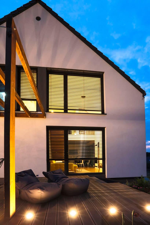 nowoczesny dom zsystemem żaluzji na oknach przy tarasie