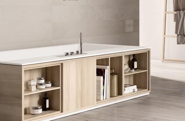 wanna zabudowana półkami na książki w jasnej łazience