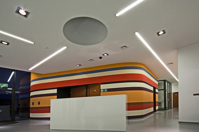 korytarz zkolorową ścianą wpaski zszybami