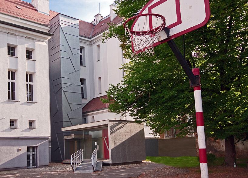 boisko do koszykówki zczerwonym koszem obok szarego budynku