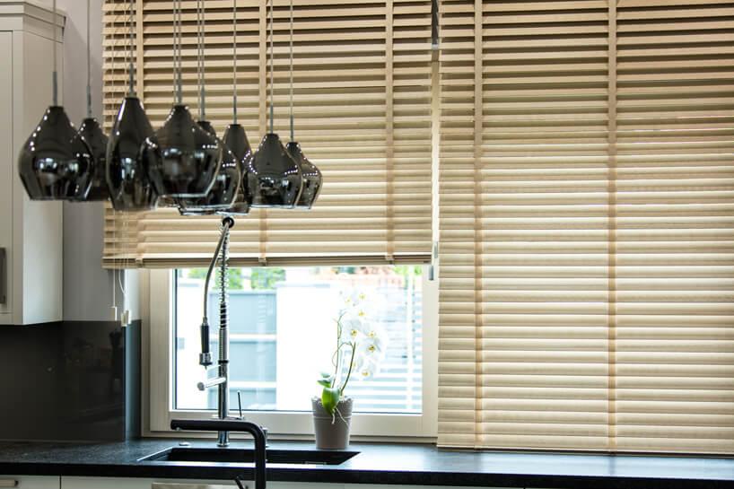 drewniane żaluzje okienne Anwis wjasnym kolorze wciemnej kuchnii
