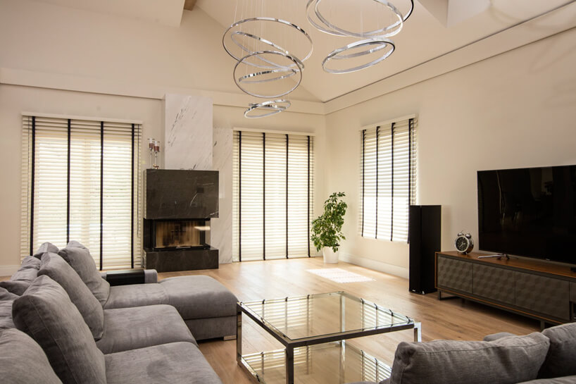 drewniane żaluzje okienne Anwis wjasnym salonie zszarą sofą