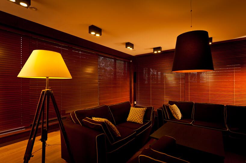 ciemno brązowe wnętrze zdrewnianymi żaluzjami okiennymi Anwis