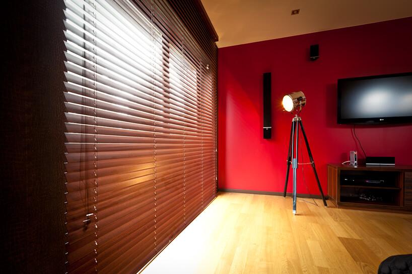 duże drewniane żaluzje okienne Anwis wsalonie zdrewniana podłoga iczerwoną ścianą