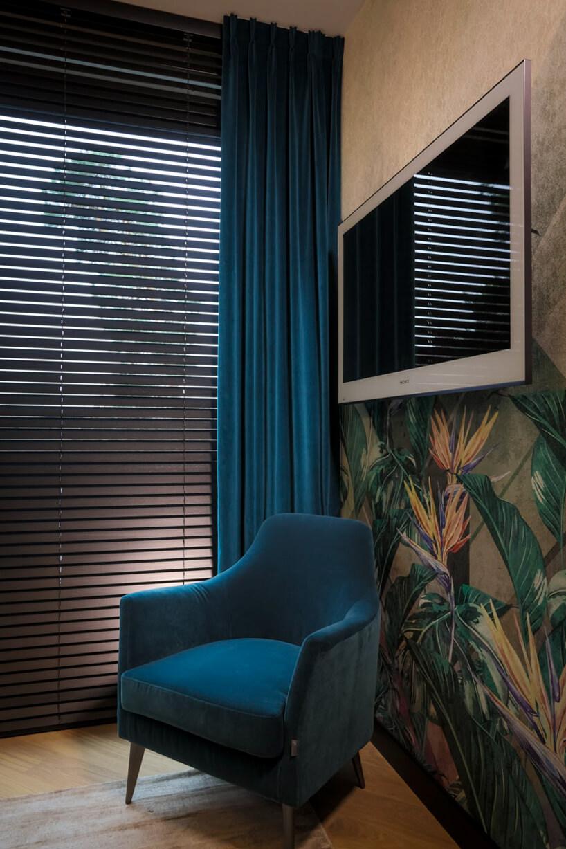 niebieski fotel na tle ciemnych żaluzji okiennych Anwis